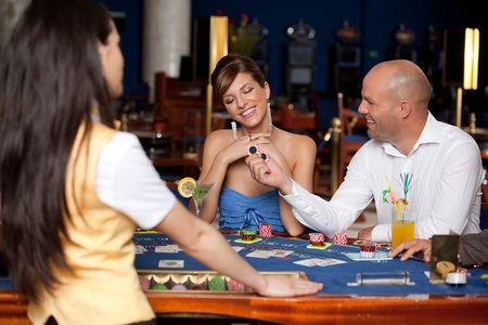 casino dealer: man offering young gorgeous woman two blackjack chips  Stock Photo