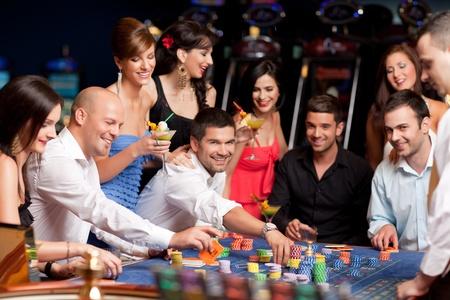 fichas casino: gente de apuestas, jugando a la ruleta en un casino de noche Foto de archivo