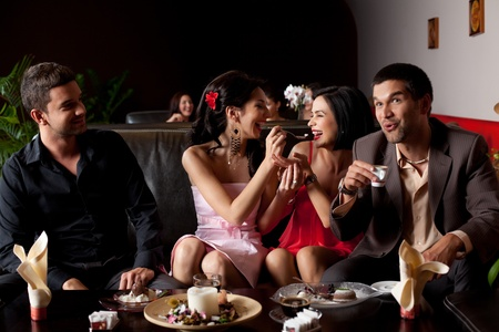 glamourous young woman laughing, feeding ice-cream to her friend Stock Photo - 10311838