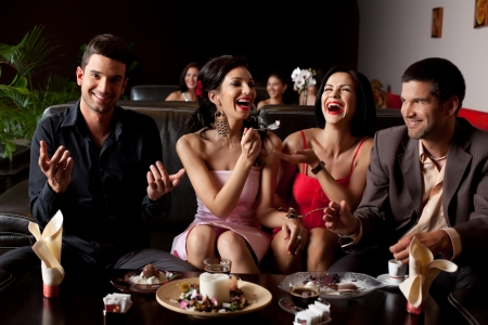 chocolate bars: glamourous young woman laughing, feeding ice-cream to her friend Stock Photo