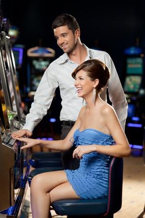 tragamonedas: pareja de jóvenes jugando juntos en la máquina de ranura