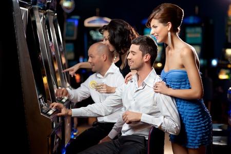 tragamonedas: amigos disfrutando jugando a las máquinas tragamonedas en el casino