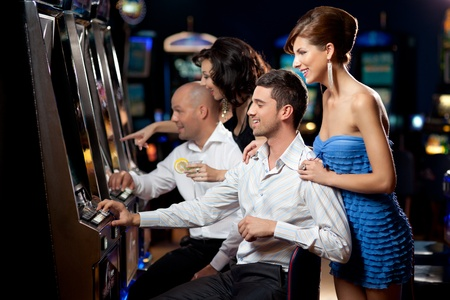 man machine: friends enjoying playing the slot machine at the casino