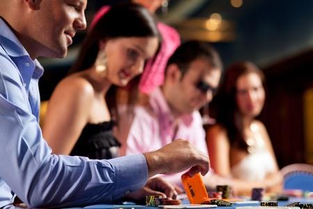 cartas de poker: jugadores sentados en la mesa, hombre sosteniendo una tarjeta de cinco mil