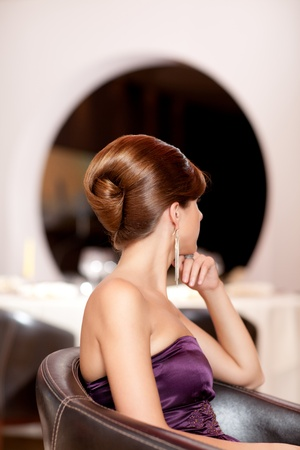 french roll: young glamourous woman with beautiful coiffure sitting in an armchair