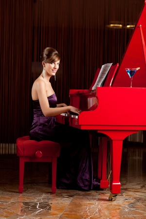 young glamourous woman playing the piano, smiling photo