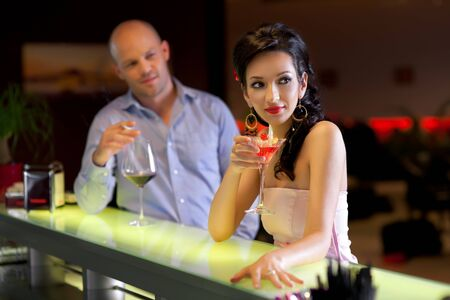 lounge bar: woman standing at the bar with men behind, looking at her
