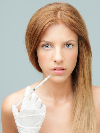 injected: young woman having colagen injected in lips