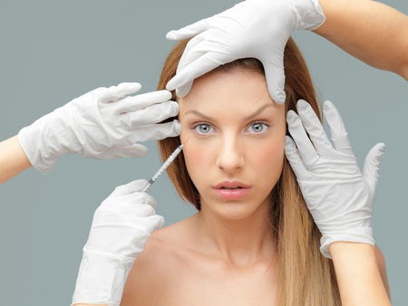 cosmetic surgery: beautiful woman having botox injected in wrinkles