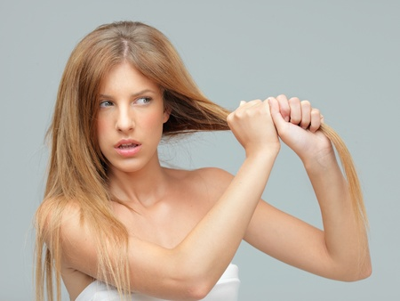 pulling hair: woman pulling damaged hair with both hands Stock Photo