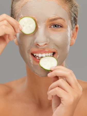 beautiful woman with mud mask cucumber slices photo