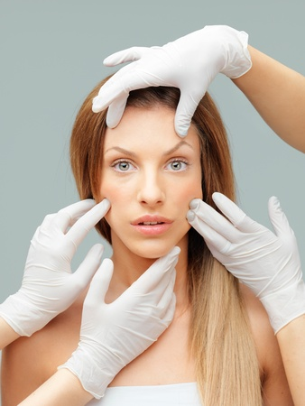 cosmetic surgery: young woman being examinated plastic surgeons hands Stock Photo