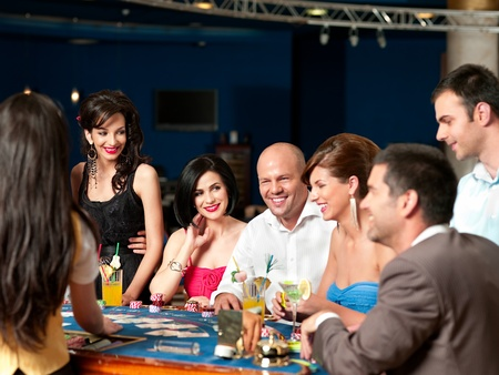casino dealer: group of people playing blackjack or poker, smiling