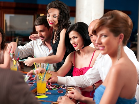 group of people playing blackjack or poker, smiling photo