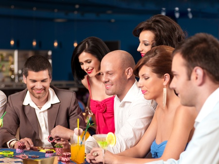 people sitting in a casino poker able, placing their bets photo