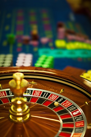 roulette wheels: closeup of a wooden roulette wheel, with betting chips behind  Stock Photo