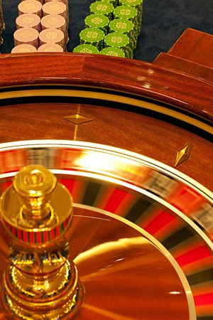 detail of a roulette wheel spinning, with betting chips behind  photo
