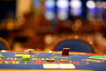 fichas casino: detalle de chips apilados en una mesa de blackjack con tarjetas en �l Foto de archivo