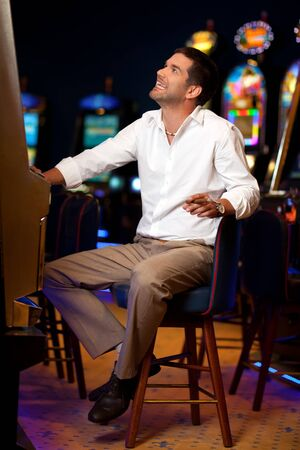 big smile: handsome man sitting by the slot machine, hoping to win