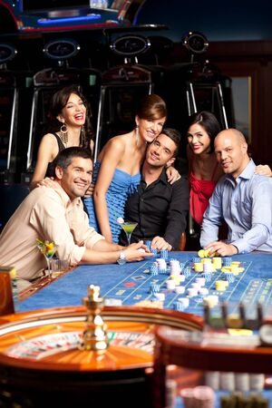 roulette player: people sitting by the roulette table, posing happy  Stock Photo