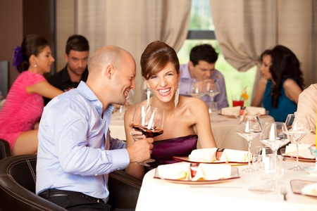 joking: young couple sitting at the restaurant table, joking over a glass of wine Stock Photo