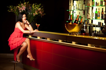 bar top: elegant woman in red sitting by the bar bored