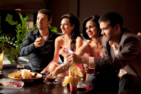 lounge bar: young couples having fun over dessert and coffee