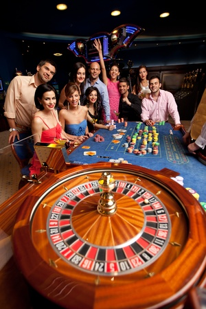 people sitting at the roulette table, watching the wheel spin