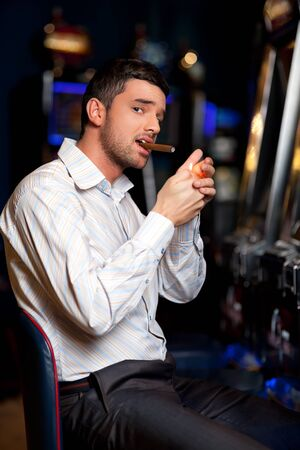 man sitting by the slot machine, lighting confident a cuban cigar Stock Photo