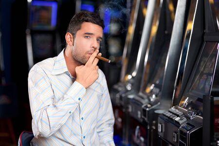 gigolo: man sitting by the slot machine, smoking confident a cuban cigar Stock Photo