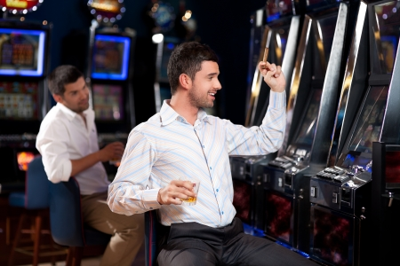 man with cigar, sitting by the slot machine, winning photo