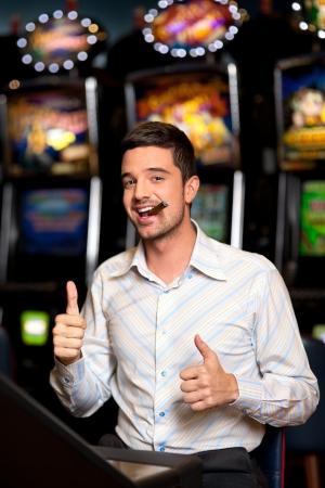 cigarro: guapo hombre fumando en un casino, está contento por ganar Foto de archivo