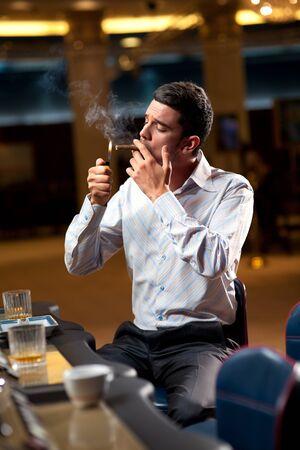 man smoking: man sitting by the slot machine, lighting confident a cuban cigar Stock Photo