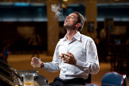 cigar smoking man: handsome man sitting by the slot machine, puffing smoke from a cuban cigar Stock Photo