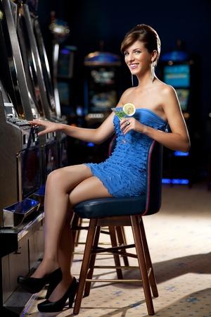 tragamonedas: joven sentada junto a la máquina tragaperras, posando con un cóctel