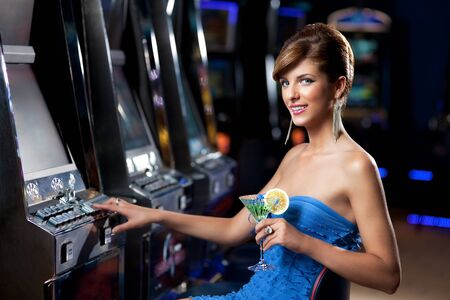 young lady sitting by the slot machine, posing with cocktail photo