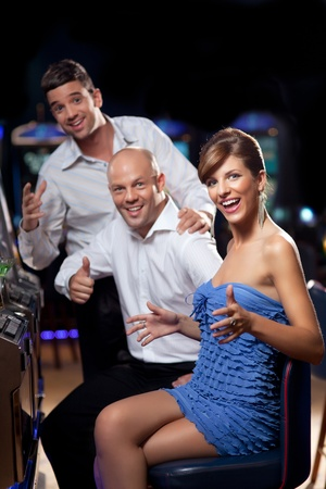 excited woman: excited woman winning at the slot machine, with happy friends cheering