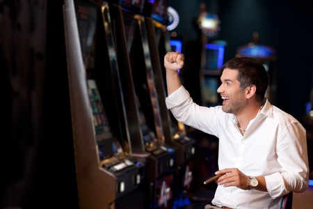 man machine: handsome business man just winning at the slot machine