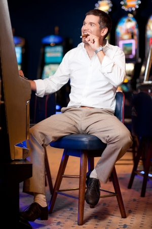 men watching excited the slot machine with cuban cigar in mouth Stock Photo - 10298325