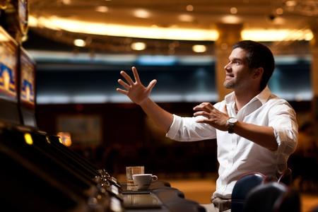 handsome man playing the slot machine, winning  photo