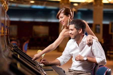 slot: elegant couple playing slot machine in casino Stock Photo