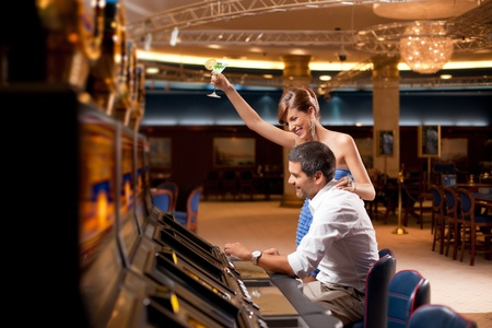 young couple winning at slot machine