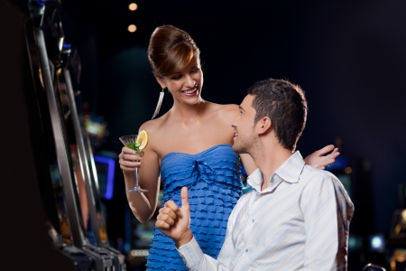 young couple sitting by the casino slot machine, looking happy to each other   Stock Photo