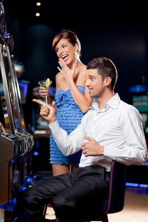 tragamonedas: joven pareja viendo salir, ganando en la máquina tragaperras
