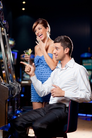 casinos: young couple watching exiting, winning at the slot machine    Stock Photo