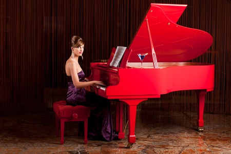 pianist: young pretty lady, playing  the piano, posing at camera