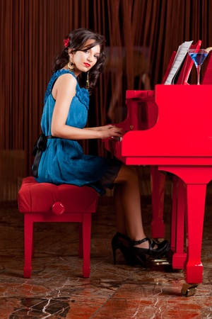 young pretty lady, playing  the piano, posing at camera Stock Photo - 10298299