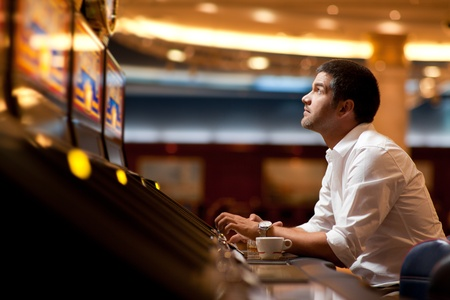 ARCADE GAMES: business man sitting at a slot machine, playing