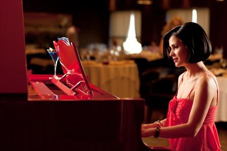 beautiful brunette woman red dress playing piano photo