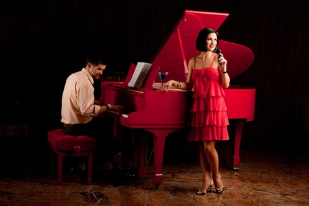 man playing piano and woman singing microphone photo